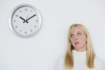 Clock-watching woman in office