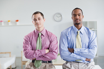 Two businessmen sitting with arms folded