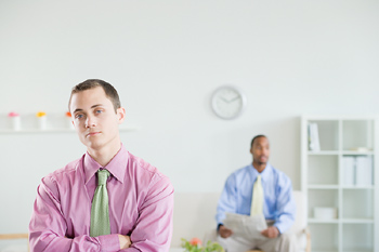 Sulking businessman in office with others