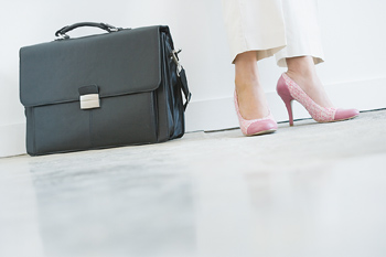 Feet of standing woman next to briefcase