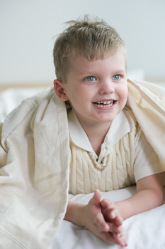Smiling boy lying down in bed