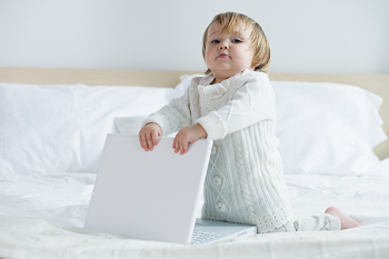 Toddler girl on bed with laptop computer