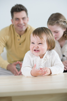 Amused toddler with family