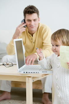 Father and daughter with laptop computer and cell phone