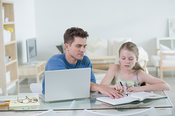 Father and daughter working at desk