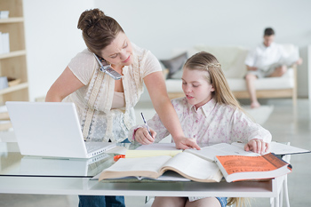 Woman with cell phone helping girl with homework
