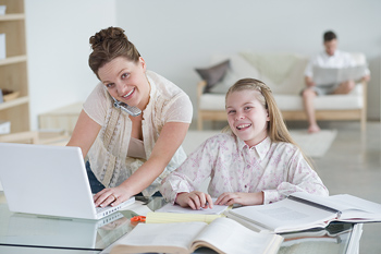 Woman with cell phone and girl sitting at desk