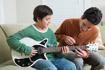 Boy learning guitar from another