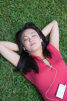 Young woman lying down with MP3 player