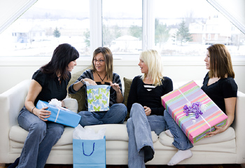 Young women on couch exchanging gifts