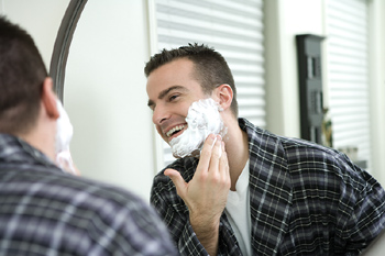 Man lathering his face with shaving cream