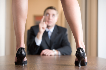 Woman standing on table as businessman scolds her