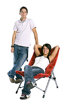 Young man and woman posing with modern chair