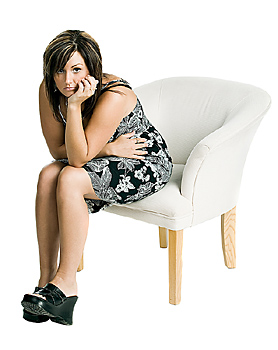 Unhappy woman in dress sitting in chair