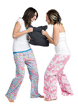 Two friends in pajamas fighting over pillow