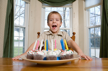 Boy blowing out candles on cupcakes