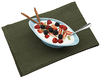 Yogurt bowl with fruit and spoon on placemat