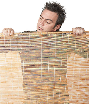Man looking over behind bamboo blind