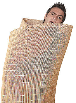 Man rolled up in bamboo blind