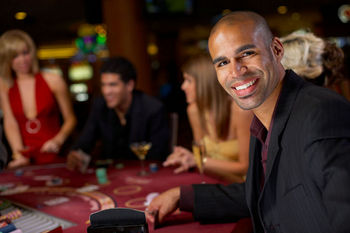 Smiling man at blackjack table with others