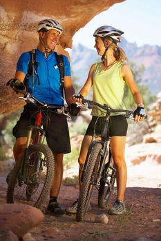 Couple on mountain bikes resting in shade