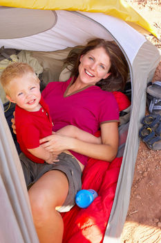 Mother and son posing inside tent