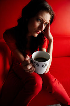 Woman holding coffee cup looking depressed