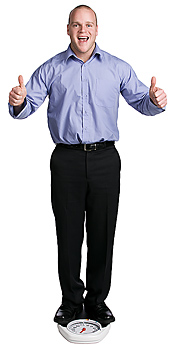 Man posing atop weight scale giving thumbs-up