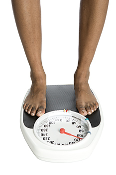 Legs of woman standing atop weight scale