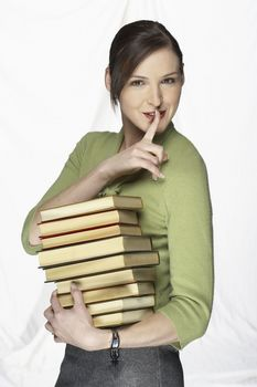Woman Gesturing to be Quiet Holding Stack of Books
