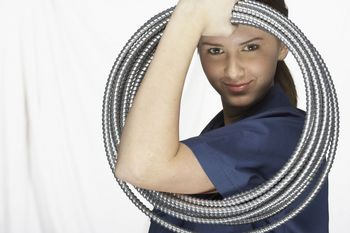 Female Worker Looking Through Coiled Hose