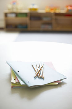 Booklets and pencils on table in classroom