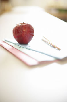 Apple with booklets and pencils