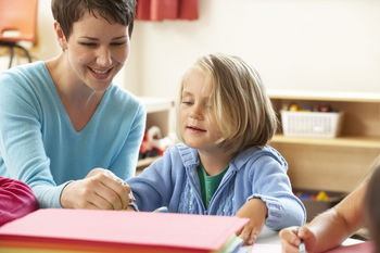 Schoolteacher helping girl with drawing