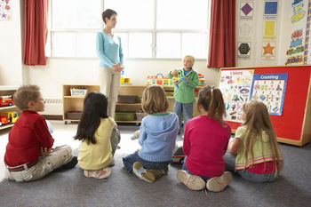 Young boy showing toy to classroom
