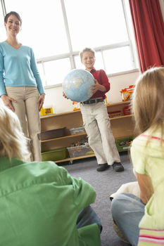 Young boy showing globe to classroom