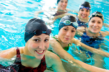 Smiling team of women swimmers in public pool