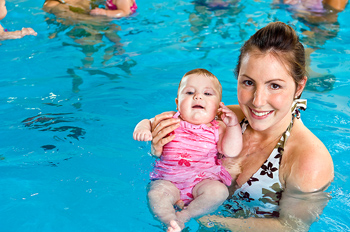 Mother and baby daughter in pool with others