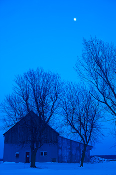 Barn in winter at night with snow