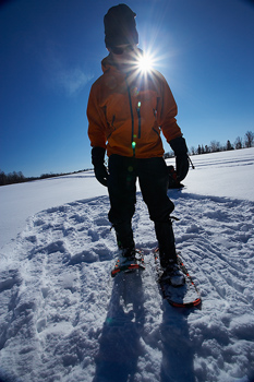 Person in snowshoes making pattern for shelter