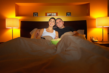 Couple in bed at home watching TV