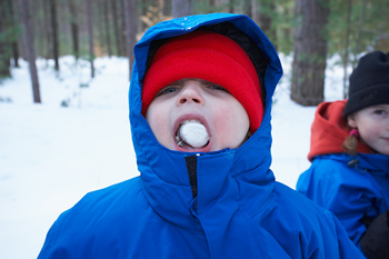 Boy eating snack outdoors in winter snow