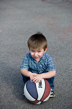 Portrait of boy with basketball outdoors