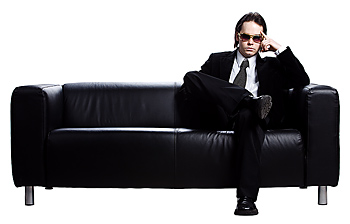 Cool businessman in sunglasses on couch