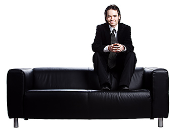 Businessman sitting atop couch