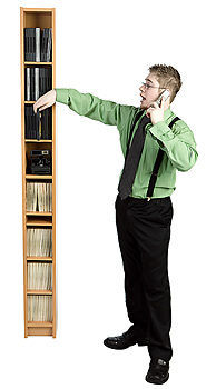 Man on cell phone by storage shelves