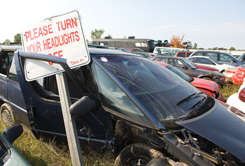 Wrecked cars in junkyard with sign
