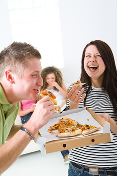 Smiling couple and friends with pizza