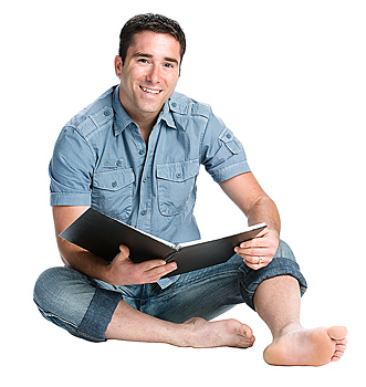 Man smiling and reading notebook