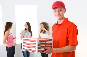 Man delivering pizza to women